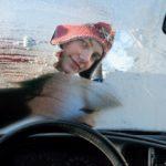 Frau kratzt Eis von ihrer Autoscheibe