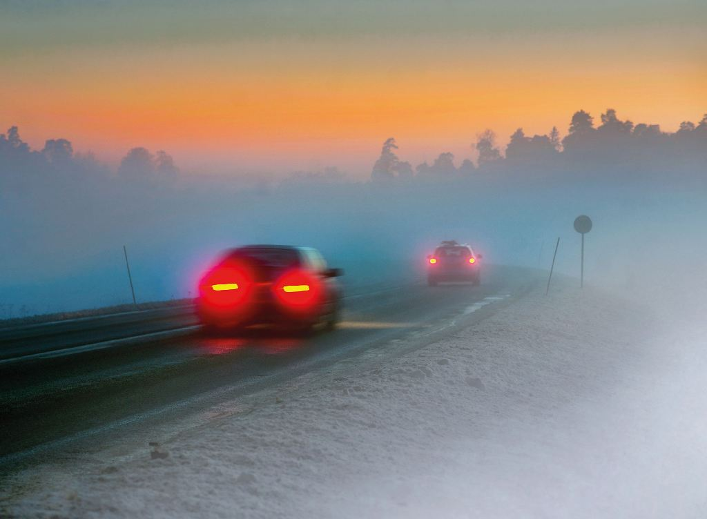 Zwei Autos auf einer nebeligen und glatten STraße