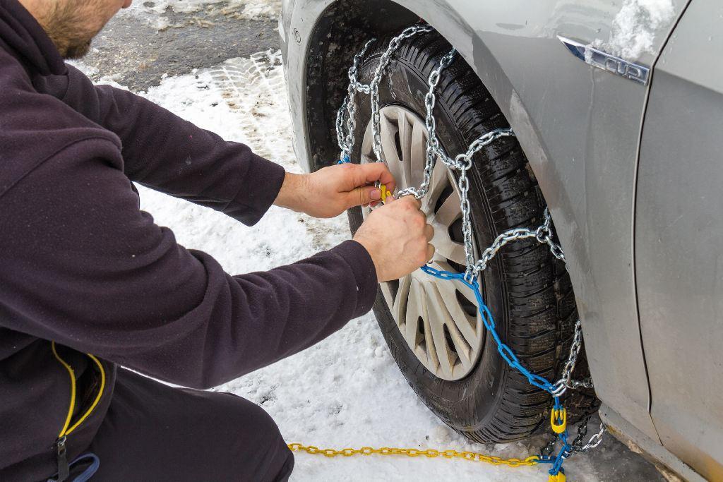 Ein Mann zieht Schneeketten auf einen Reifen