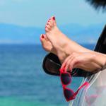 Ferienauto am Meer: Zwei füße mit roten Fußnägeln, eine Hand mit Sonnenbrille ragen aus dem Autofenster.