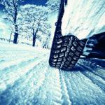 Nahaufnahme eines Mietwagen mit Winterreifen auf schneebedeckter Fahrbahn (Winterreisen).