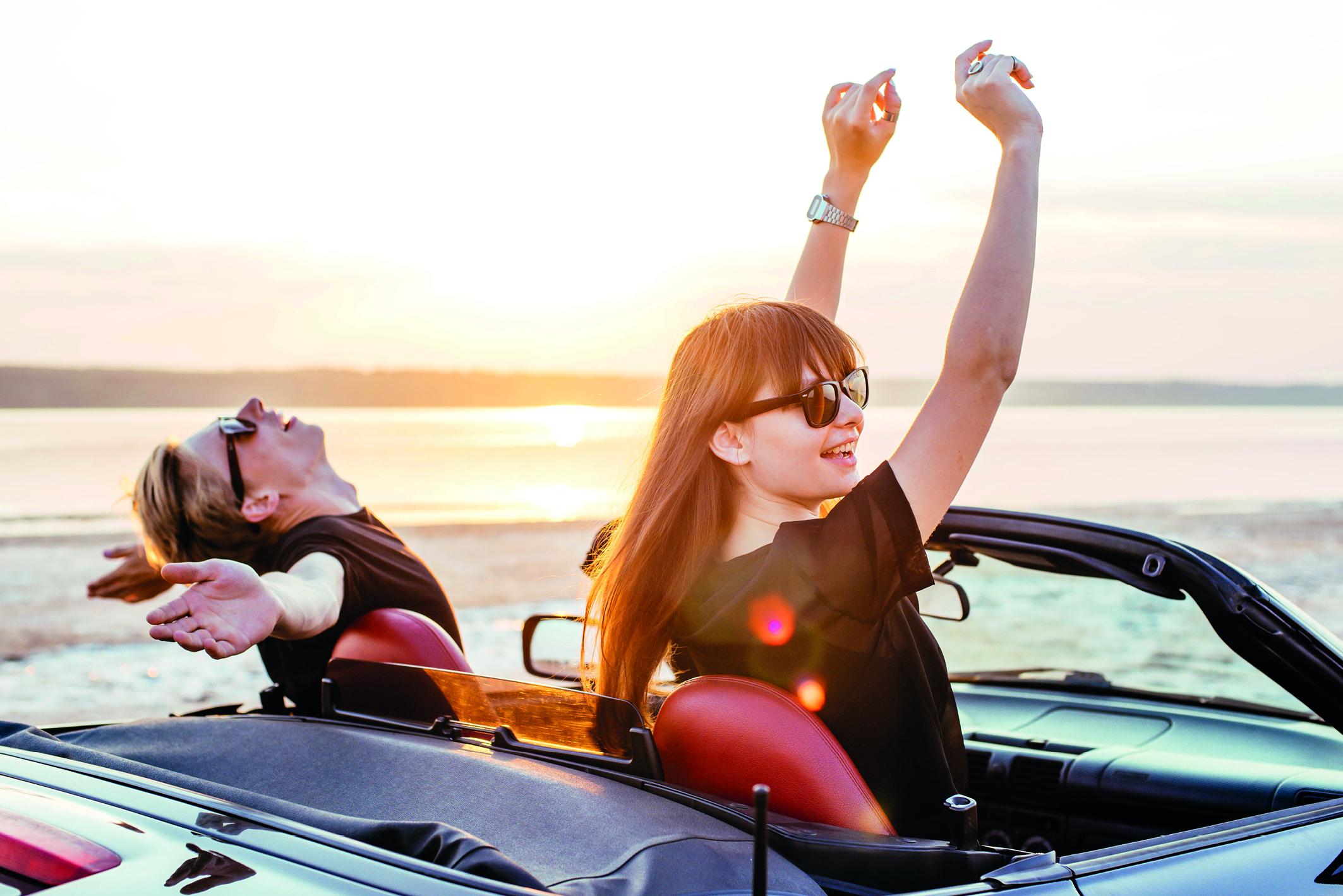 Junge Frau und junger Mann in einem Caprio (Mietwagen) am Meer.