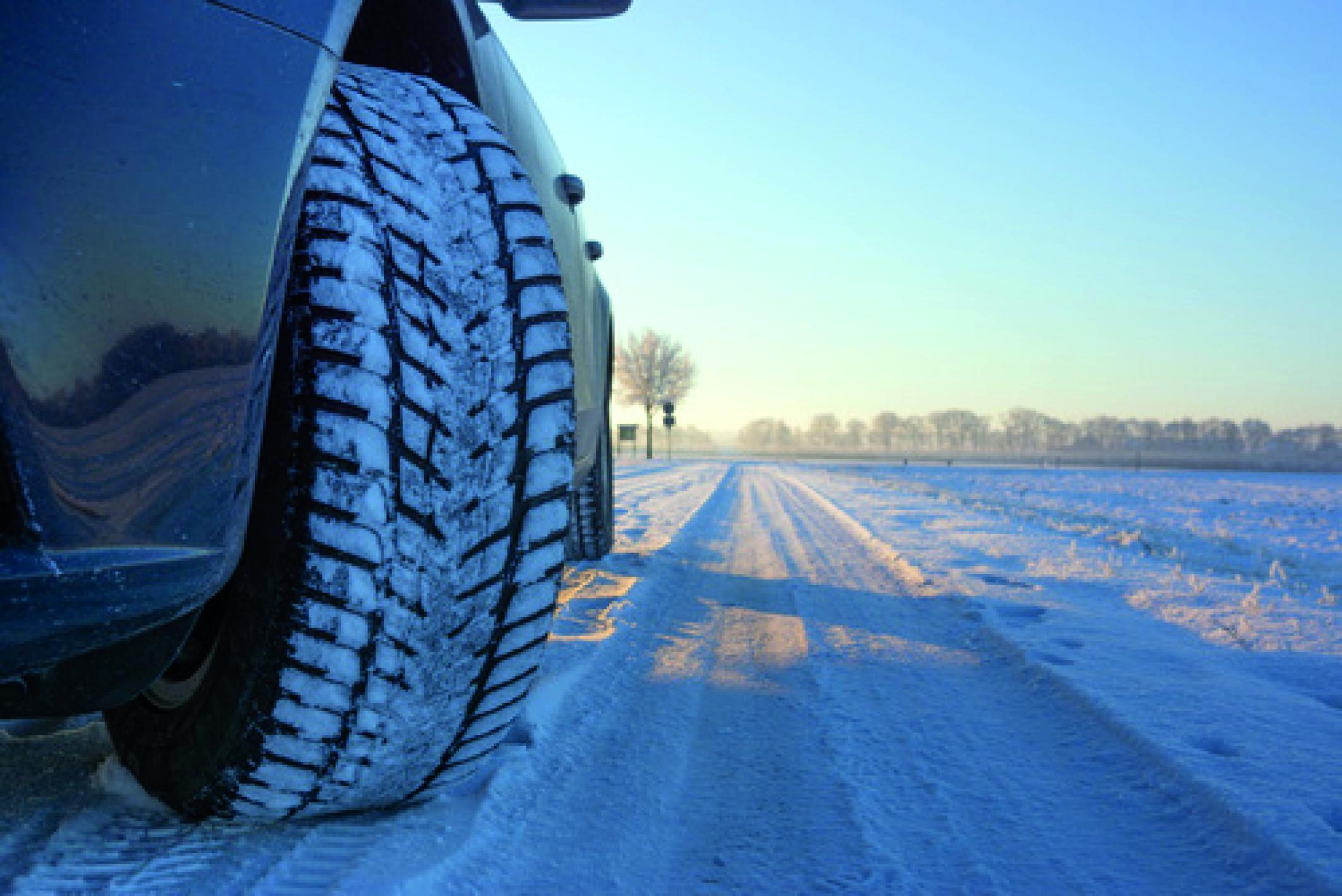 Nahaufnahme- Profil eines Winterreifen auf schnee- und eisbedeckter Fahrbahn