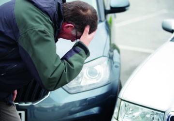 Ein Mann schaut sich verzweifelt zwei Autos an, die aneinander geprallt sind. (Fahrerflucht)