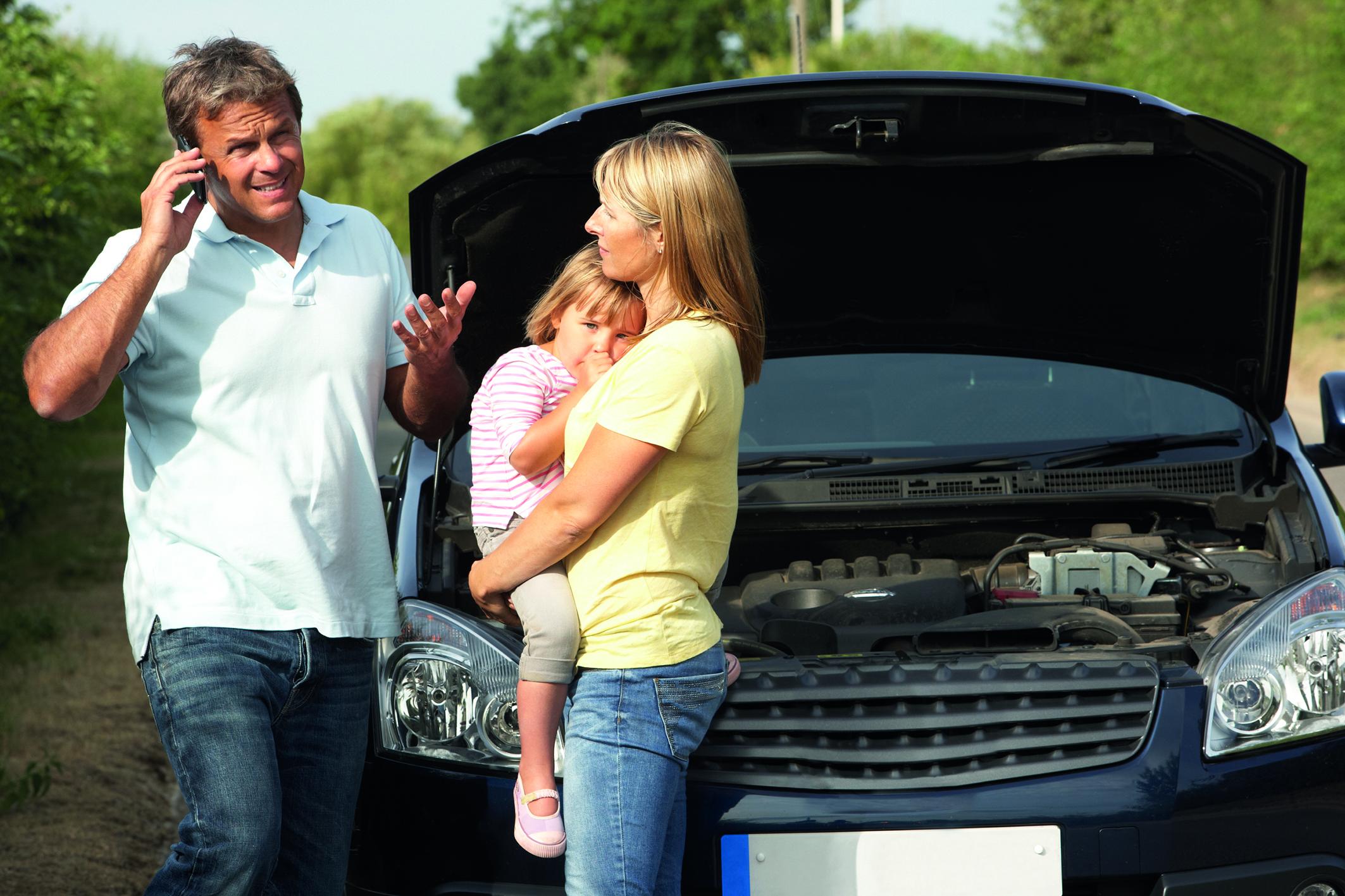Die Motorhaube eines Autos steht offen, ein Mann telefoniert mit seinem Smartphone und eine Frau trägt ein kleines Kind auf dem Arm. (Schutzbrief bei Autopanne)