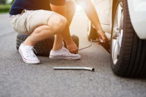 Ein Mann wechselt den Reifen eines Autos (Autoreifen selber wechseln).