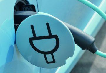 Ein blaues Elektroauto wird an einer speziellen Steckdose aufgeladen.
