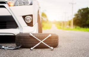 Ein Autoreifen liegt mit einem Radmutternschlüssel vor einem Auto, auf der Straße (Autoreifen selber wechseln).