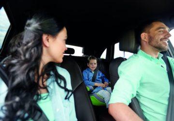 Eine Familie fährt gemeinsam im Auto. Die Frau schaut zurück auf die Rückbank zu einem kleinen Jungen (Fahrzeug prüfen)