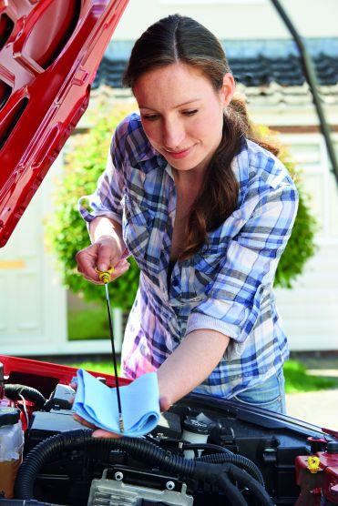 Eine Frau prüft ihr Fahrzeug, indem sie den Ölstand misst.