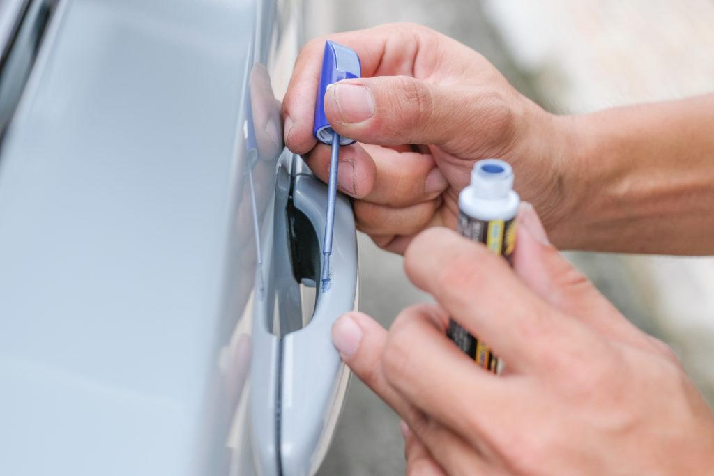Autopflege im Frühjahr: mithilfe eines Lackstiftes wird ein Kratzer im Autolack ausgebessert.