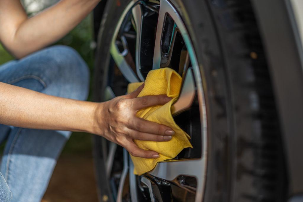 Autopflege im Frühjahr: Autoreifen werden mithilfe eines gelben Tuches gesäubert.