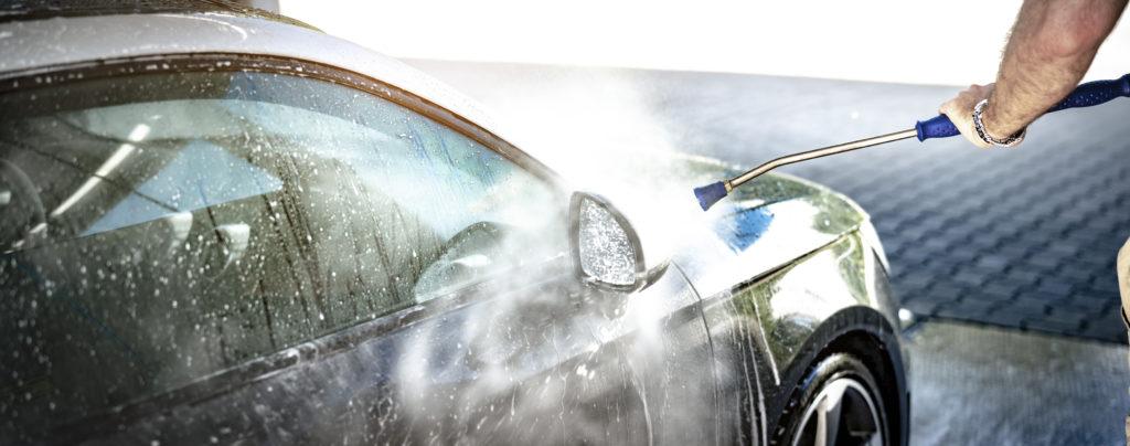 Autopflege im Frühjahr: ein Mann reinigt sein Auto mithilfe eines Hochdruckreinigers.