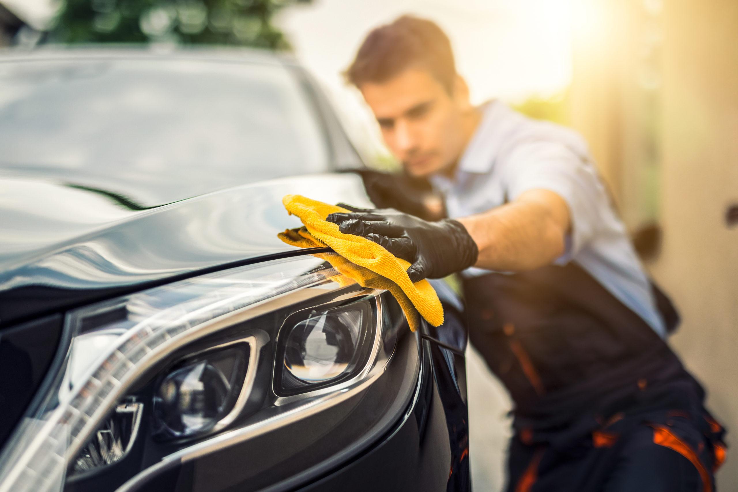 Regelmäßige Autopflege: ein Mann poliert sein Auto mit einem gelbem Tuch.