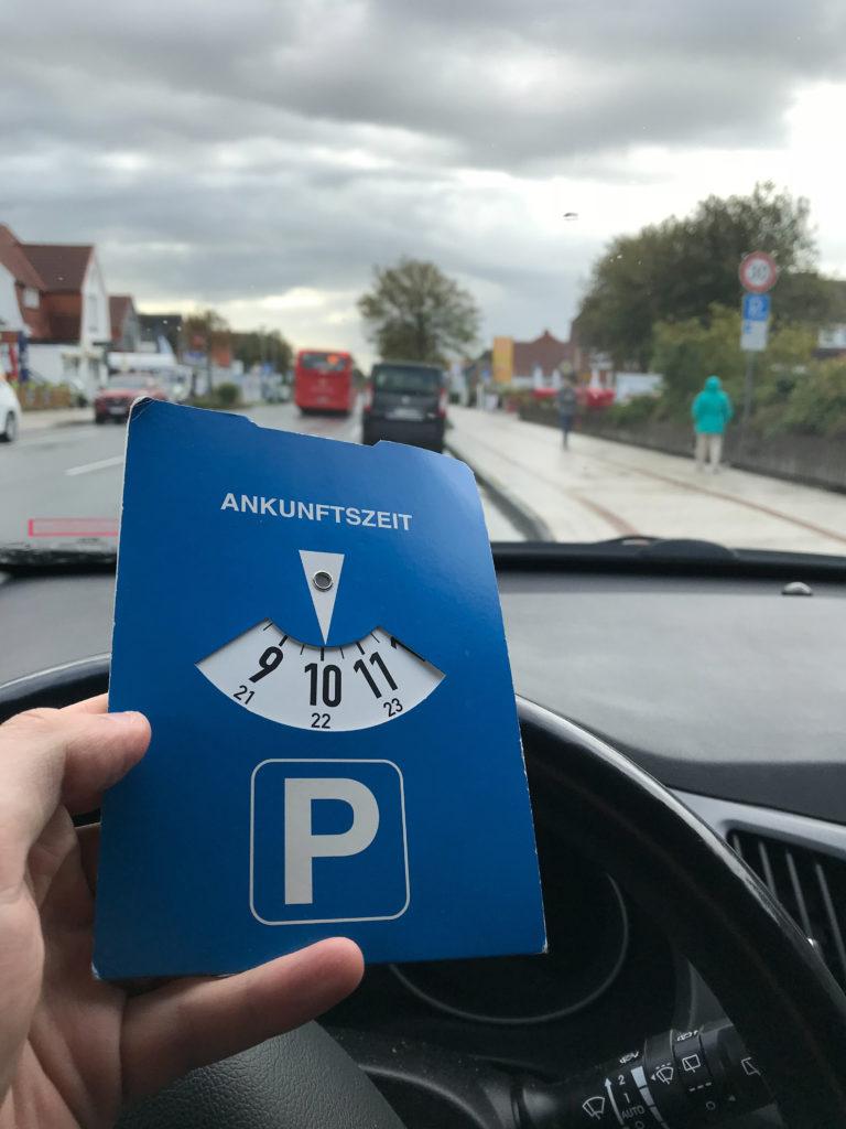 Neuer Bußgeldkatalog 2020: ein Autofahrer parkt auf einem Seitenstreifen und hält eine blaue Parkscheibe in der Hand.