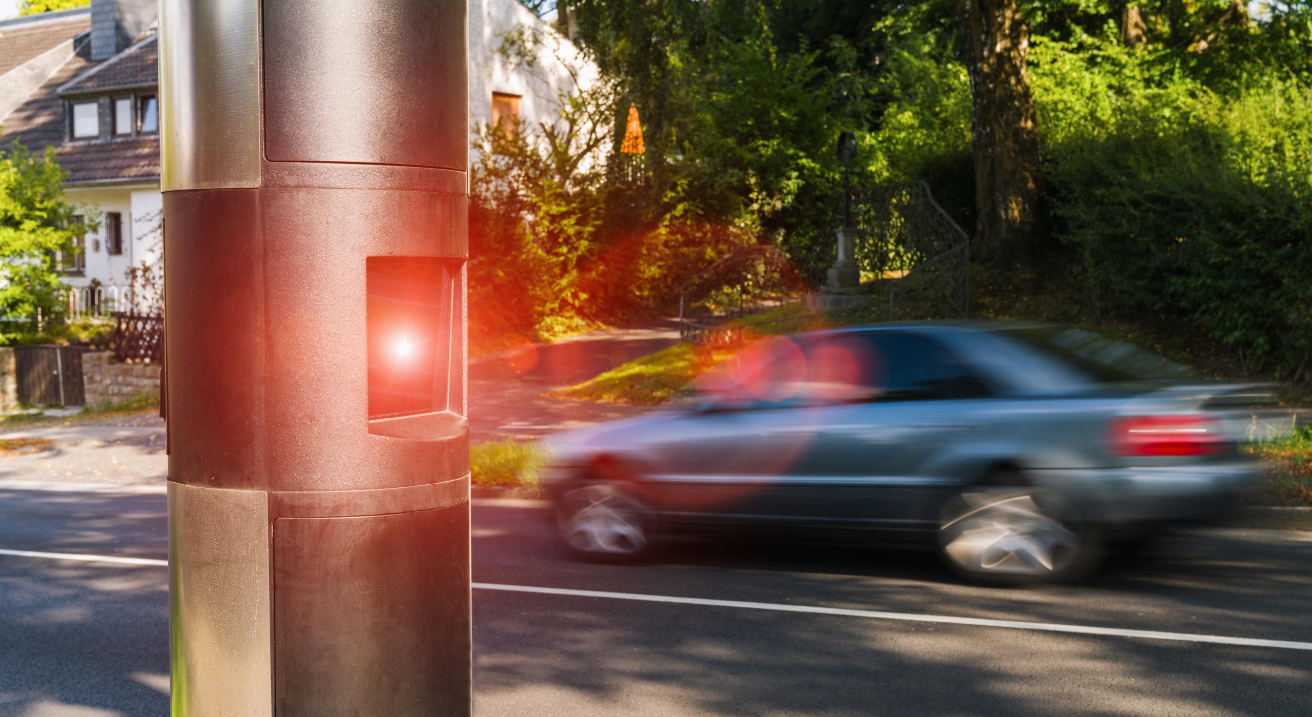 Neuer Bußgeldkatalog 2020: ein schnelles Auto wird von einem Blitzer fotografiert.